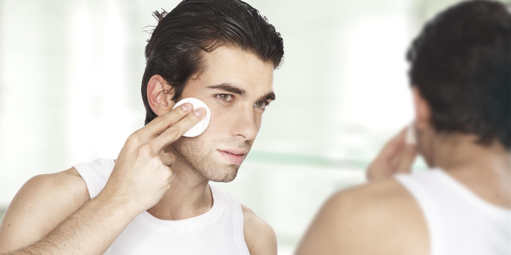 Man looking at his reflection; using facial toner